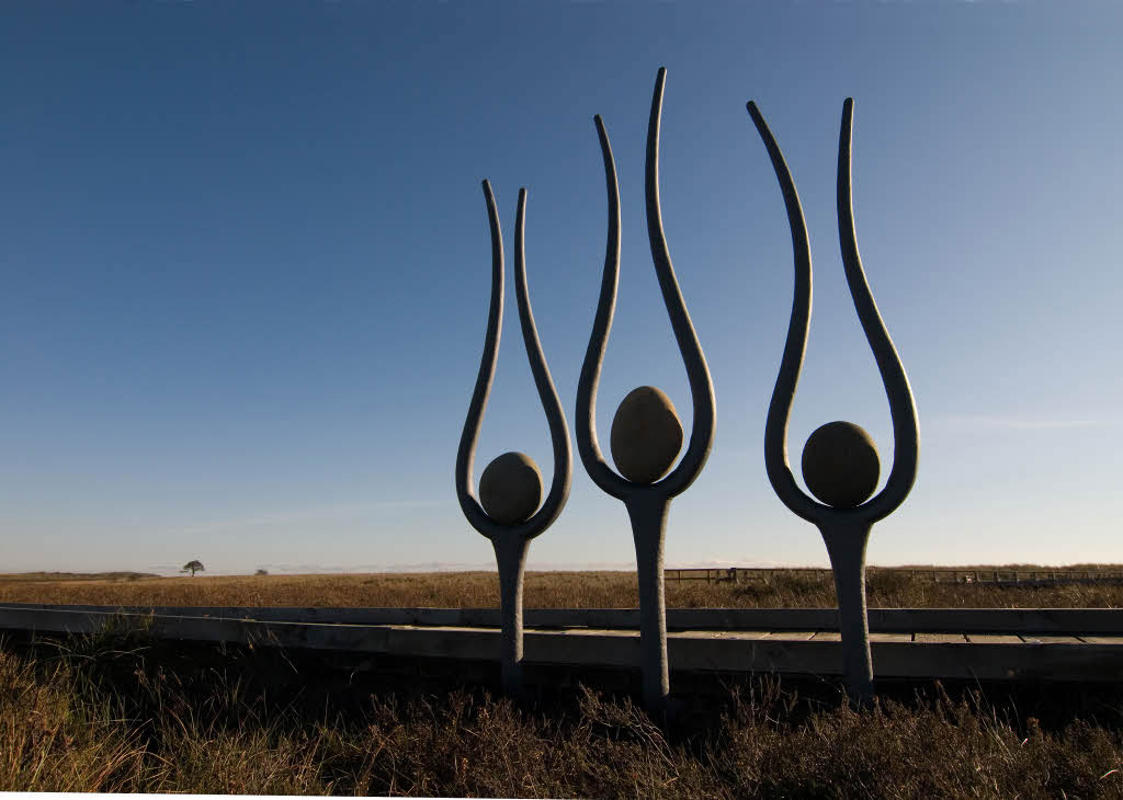 A sculpture of three sinuous forms like tuning forks, with an egg-like stone in the centre of each.