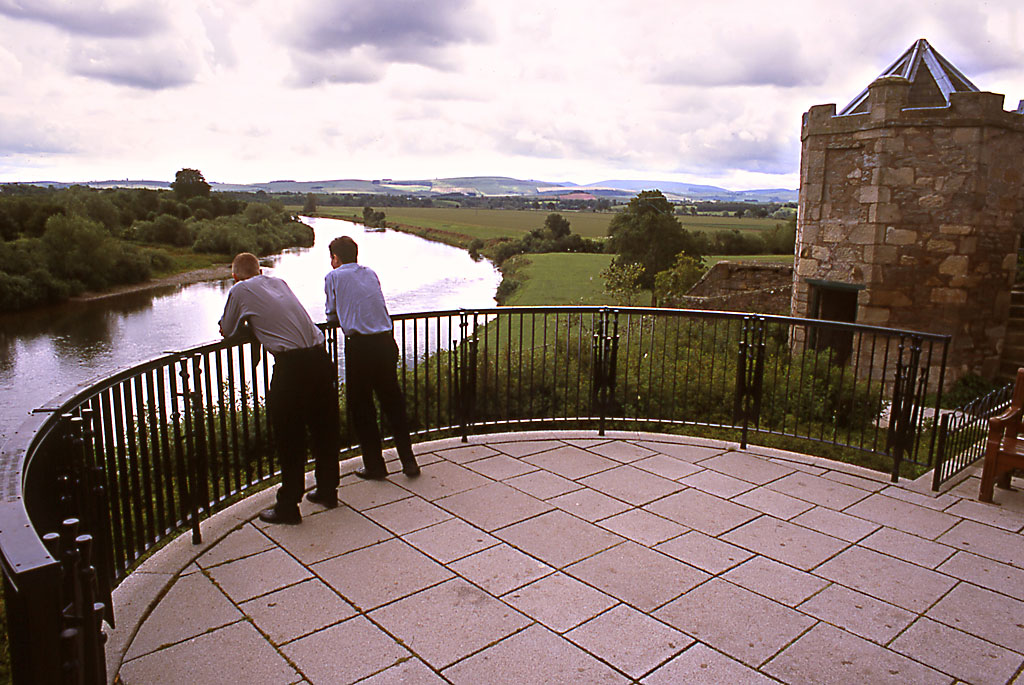 Two men lean over a curved railing above a sweep of a river.
