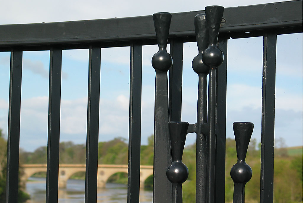 A stone bridge over the river tweed is seen through black railings, which include a design inspired by a thistle.