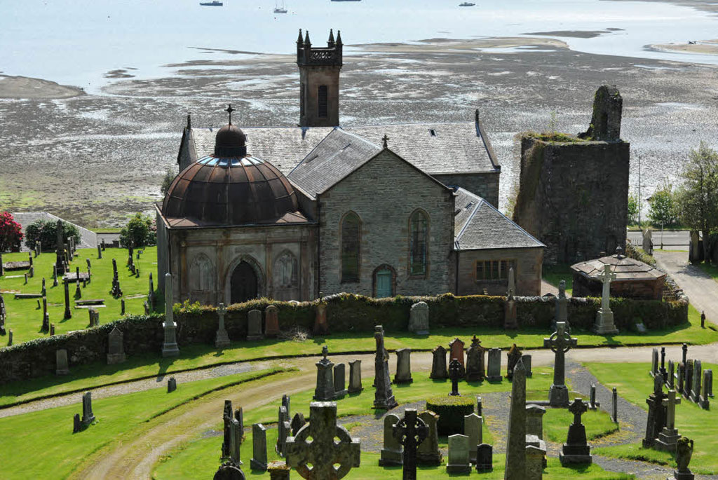 St Munn's church, Kilmun, with the Argyll Mausoleum and ruins of collegiate church, against a background of the sunlit Holy Loch.