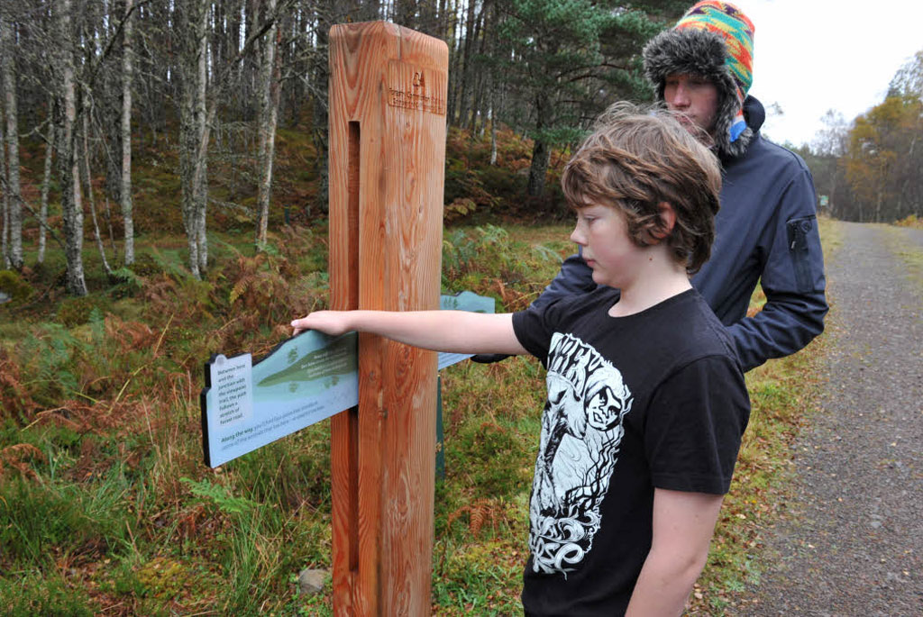 Two boys read a semaphore-arm panel beside a trail through a forest.