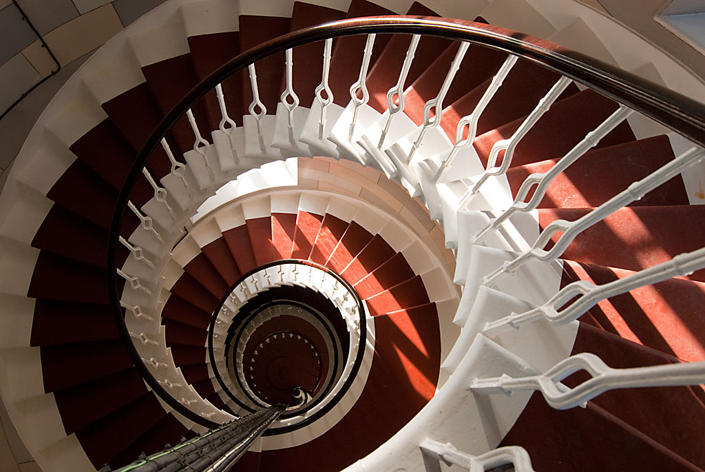 A view down a spiral staircase, the steps carpeted in red and with white-painted edges.