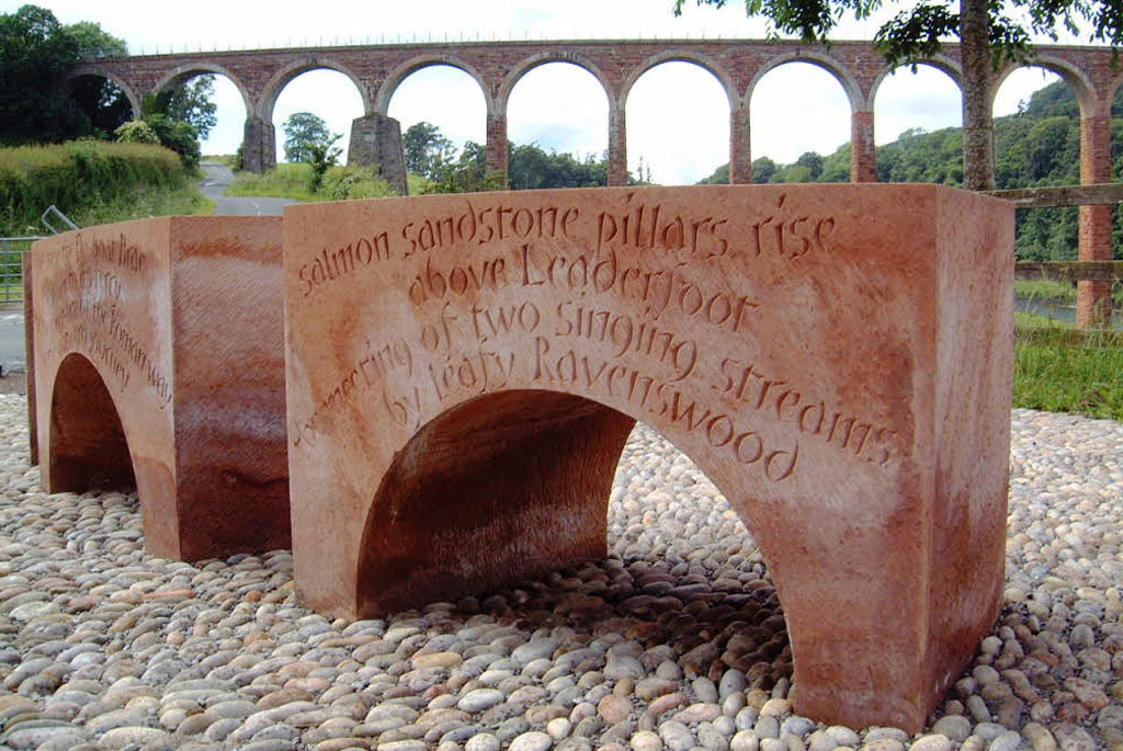 A block of red sandstone carved into an arch, with a poem deeply engraved into the surface.