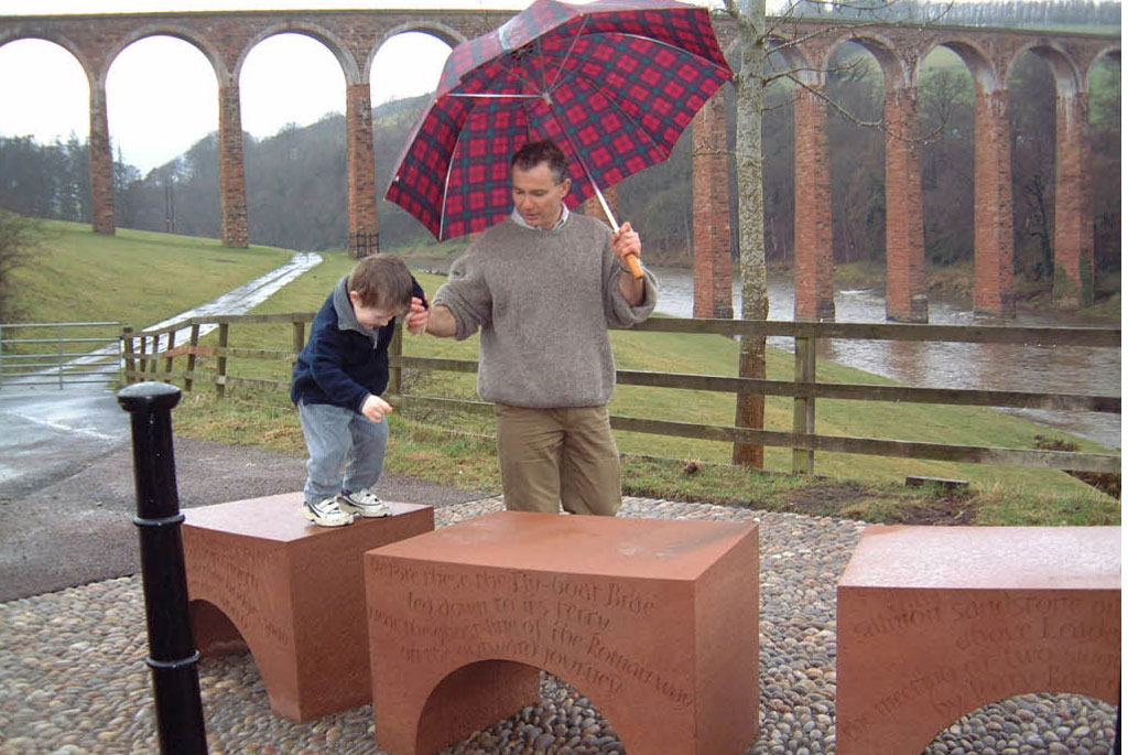 A man holding an umbrella guides a small boy who is jumping from one carved stone arch to another.