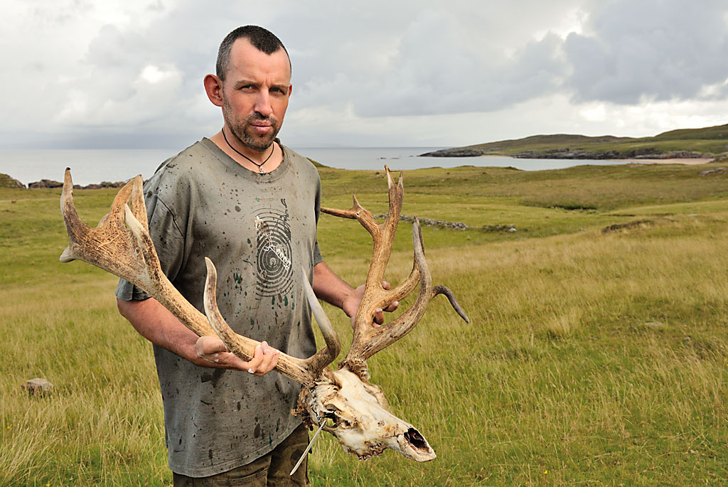 A man with close-cropped black hair, holding a large red deer skull with branching antlers.
