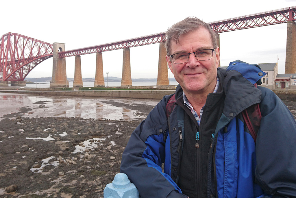 A photograph of James Carter with the Forth rail bridge in the background.